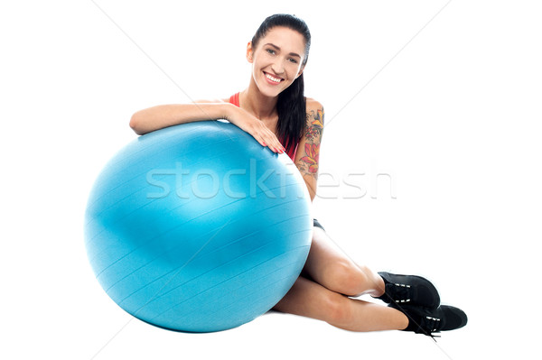 Woman in gym relaxing beside exercise ball Stock photo © stockyimages