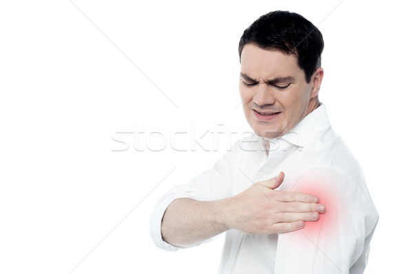 Young man suffering from shoulder pain Stock photo © stockyimages