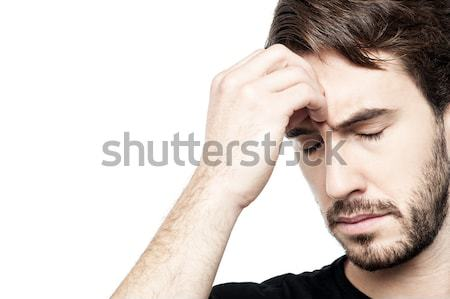 Young man holding head in hand Stock photo © stockyimages