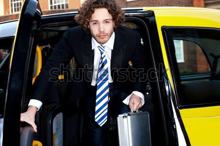 Male passanger getting out of a taxi cab Stock photo © stockyimages