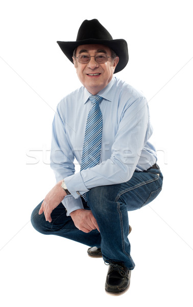 Stock photo: Image of a senior cowboy posing semi seated
