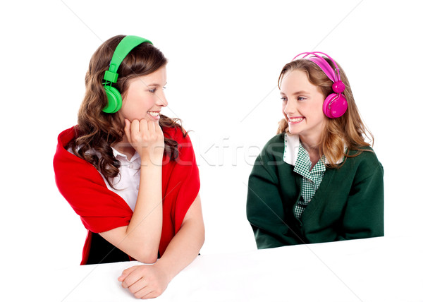 Pretty girls enjoying music. Looking at each other Stock photo © stockyimages
