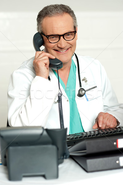 Matured physician communicating on phone Stock photo © stockyimages