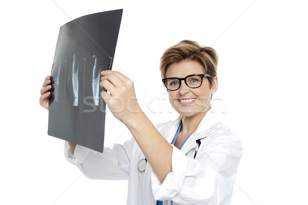 Experienced female doctor examining x-ray report Stock photo © stockyimages