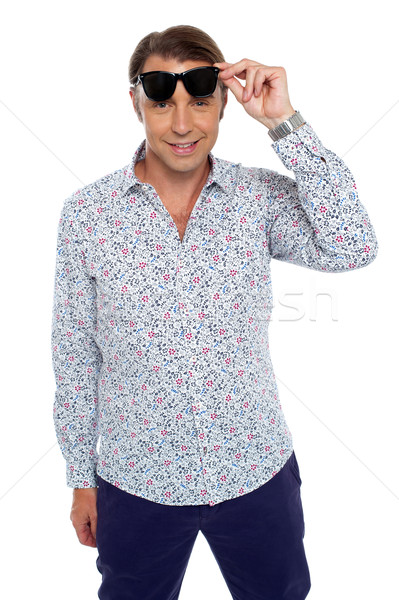 Confident casual man taking off his dark shades Stock photo © stockyimages