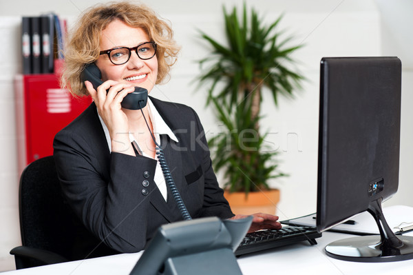 Happy front desk lady attending clients call Stock photo © stockyimages