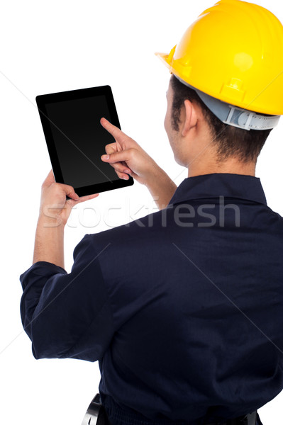 Back pose of worker operating tablet device Stock photo © stockyimages