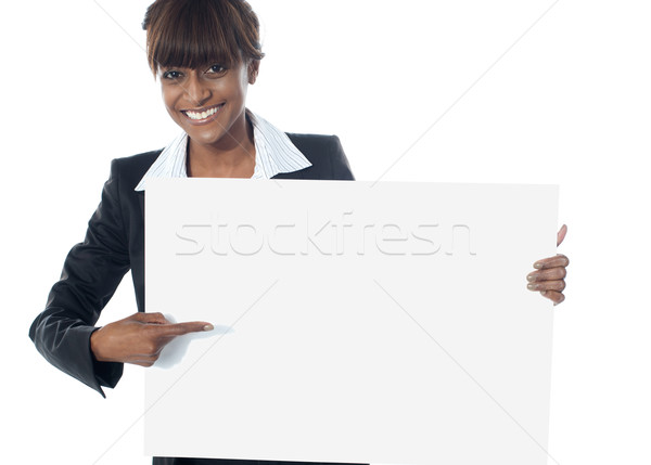 Corporate female executive pointing towards blank banner Stock photo © stockyimages