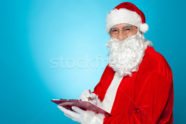 A thoroughly modern Santa claus checks his list on clipboard Stock photo © stockyimages