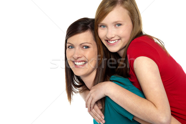 Mother giving daughter ride on back Stock photo © stockyimages