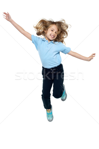 Energetic young child jumping high Stock photo © stockyimages