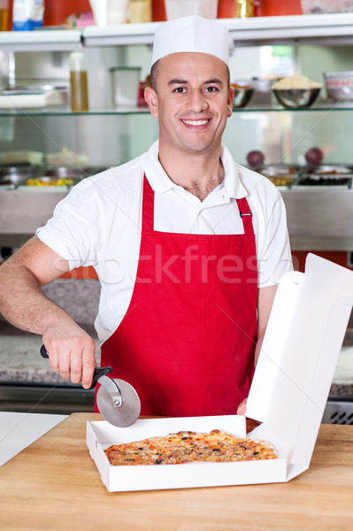 Chef holding pizza cuter, ready to cut. Stock photo © stockyimages