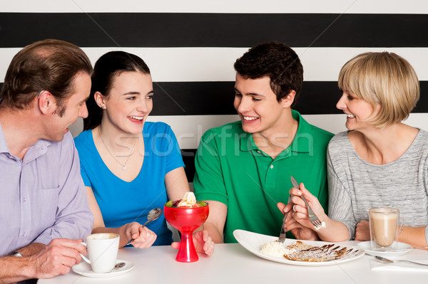 Happy family of four in restaurant Stock photo © stockyimages