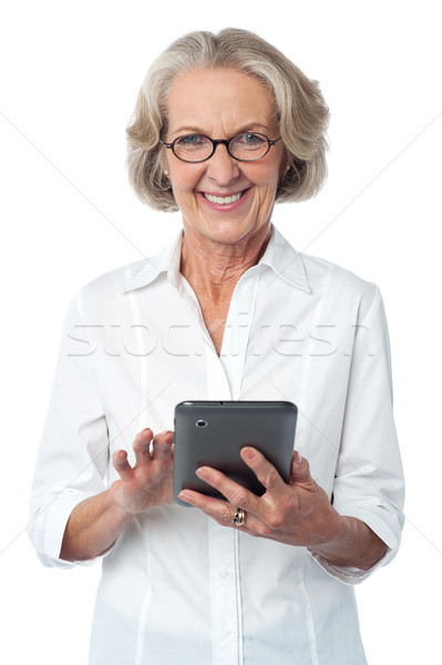 Aged woman using touch pad device Stock photo © stockyimages