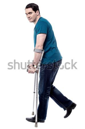 Ferido homem muletas lado pose casual Foto stock © stockyimages
