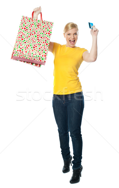 Excited teenager holding shopping bag and card Stock photo © stockyimages