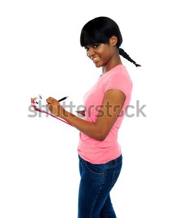 Glimlachend meisje schrijven geïsoleerd witte Stockfoto © stockyimages