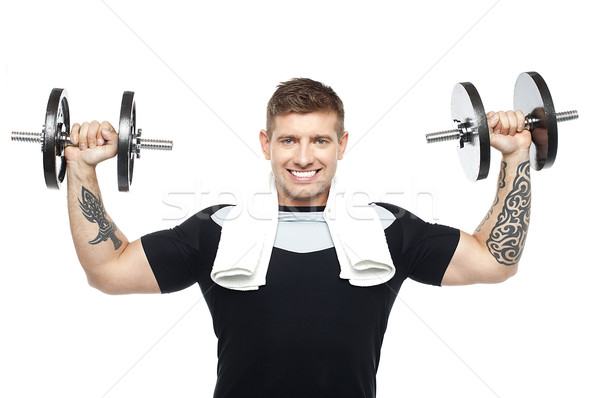 Young bodybuilder exercising, toning his biceps Stock photo © stockyimages