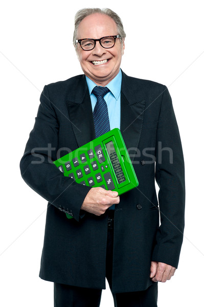 Senior male manager holding big green calculator Stock photo © stockyimages