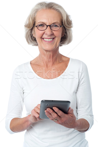 Aged woman with touch pad device Stock photo © stockyimages