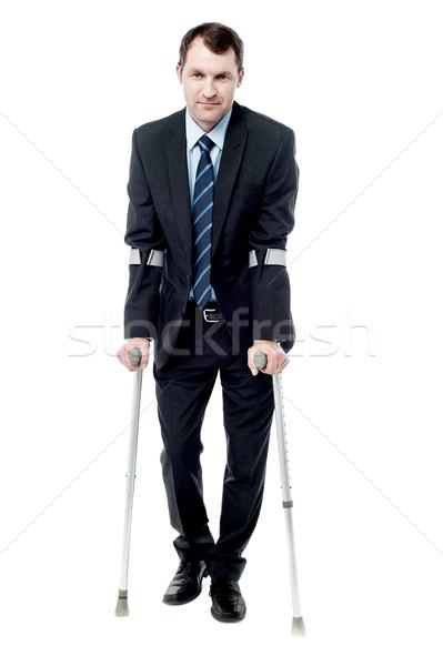 Inteligente homem muletas andar empresário caminhada Foto stock © stockyimages