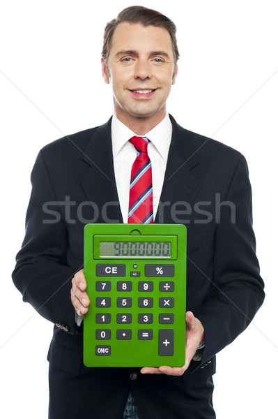 Young businessman showing big green calculator Stock photo © stockyimages
