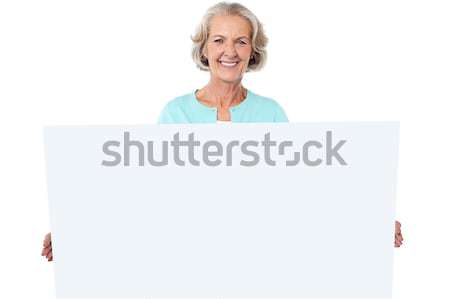 Casual old lady holding a blank billboard Stock photo © stockyimages