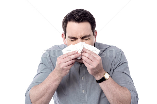 Sick man sneezing Stock photo © stockyimages