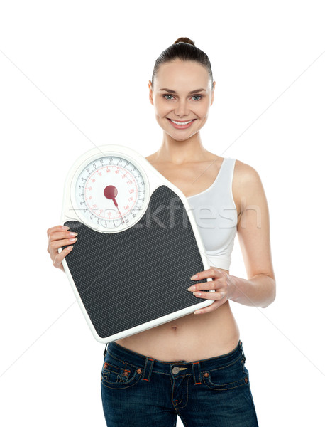 Healthy young woman with a weighing scale Stock photo © stockyimages