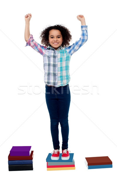 Excited pretty school child standing on books Stock photo © stockyimages
