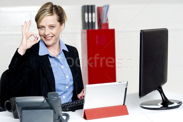 Female executive showing excellent gesture Stock photo © stockyimages