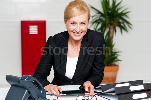 Smiling corporate lady holding wireless tablet Stock photo © stockyimages