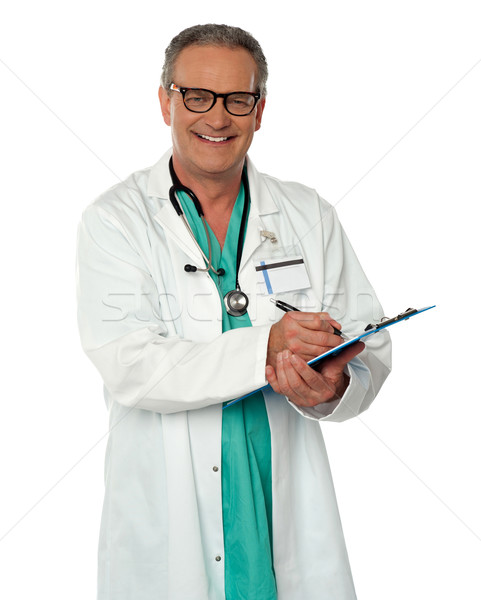 Experienced male doctor making report Stock photo © stockyimages