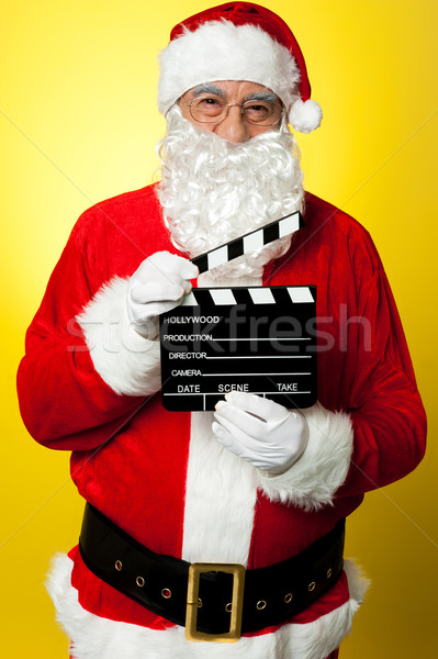 Cheerful Kris Kringle posing with clapperboard Stock photo © stockyimages