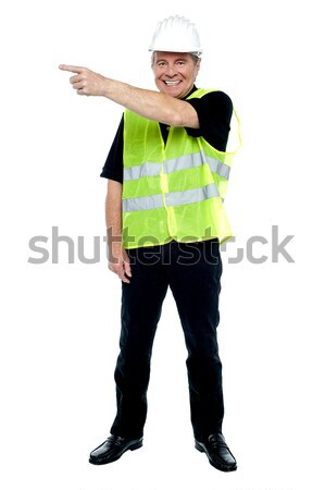 Cheerful estate engineer indicating sideways Stock photo © stockyimages