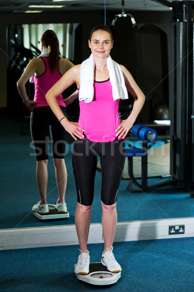 Slim lady measuring her weight Stock photo © stockyimages