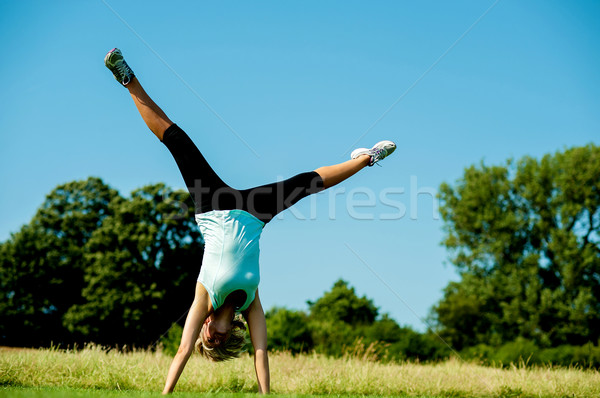 Woman doing cartwheel in a field Stock photo © stockyimages