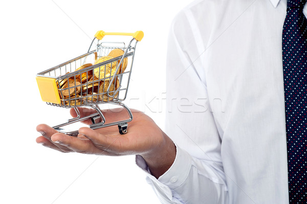 Man holding a shopping cart filled with gold coins Stock photo © stockyimages