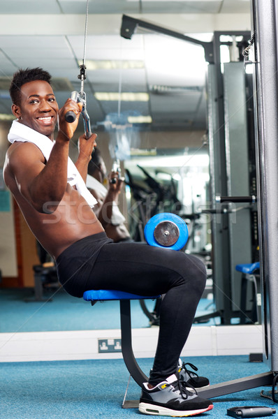 Fit african trainer working out in multi gym Stock photo © stockyimages
