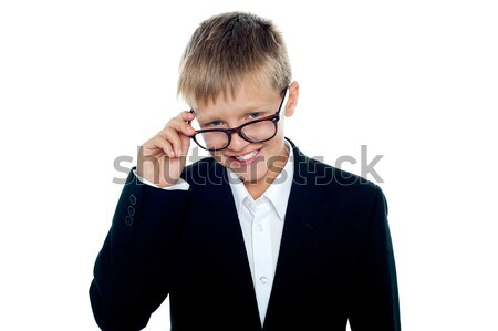 Young business boy looking through his glasses Stock photo © stockyimages