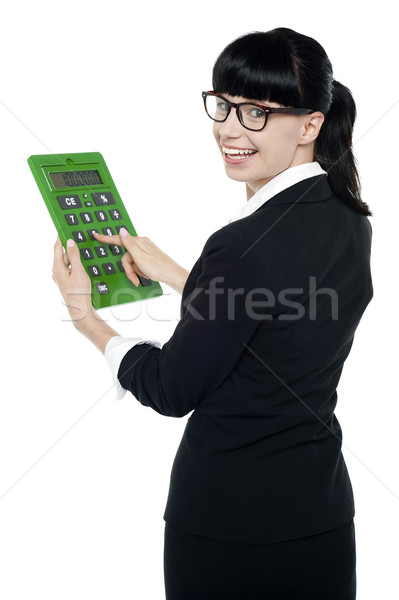 Bespectacled woman turning back, holding calculator Stock photo © stockyimages