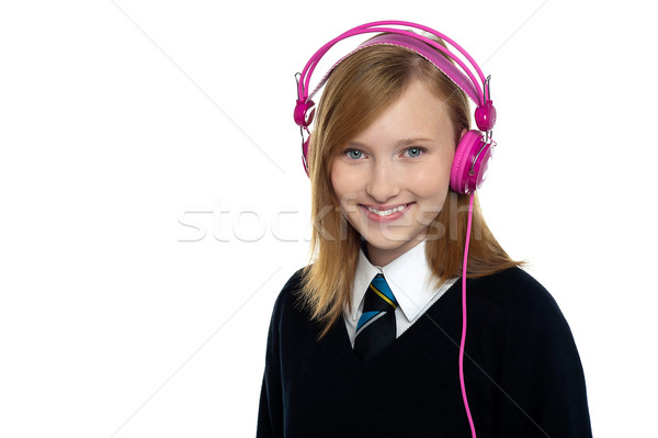 Cute teenager listening to music through headphones Stock photo © stockyimages