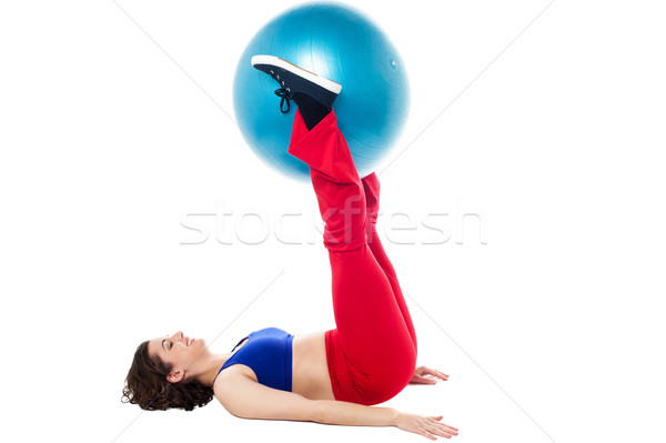 Fit woman holding exercise ball between legs Stock photo © stockyimages
