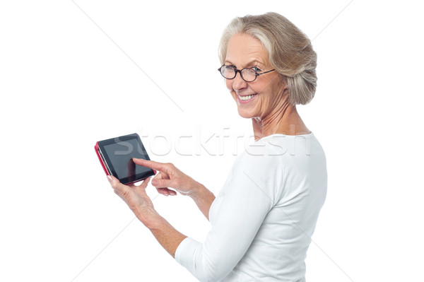 Aged lady operating touch pad device Stock photo © stockyimages