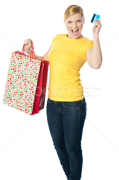 Happy shopaholic girl showing credit card Stock photo © stockyimages
