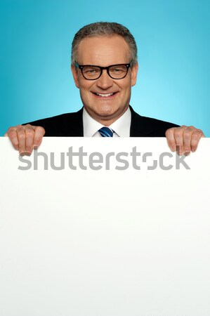 Young man holding blank billboard Stock photo © stockyimages