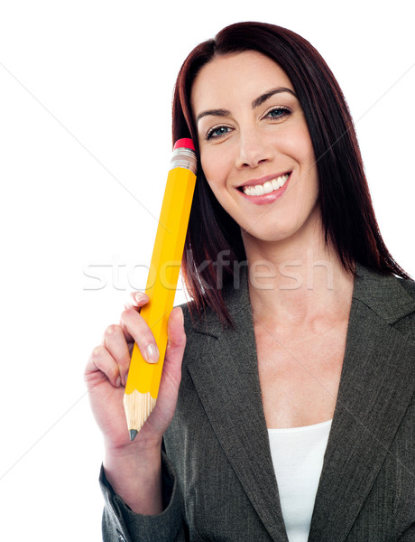 Thoughtful businesswoman holding big pencil Stock photo © stockyimages