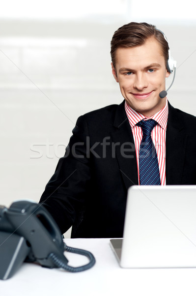 Male executive wearing headsets and smiling Stock photo © stockyimages