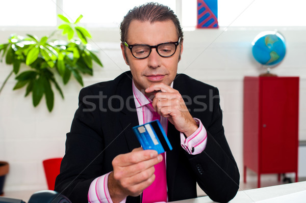 Corporate man staring at his credit card Stock photo © stockyimages
