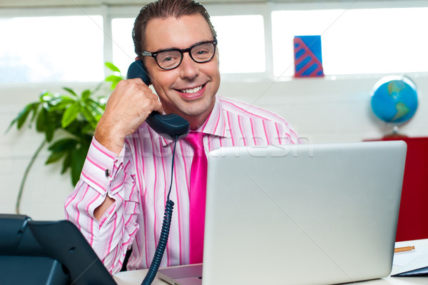 Happy executive engaged on a business call Stock photo © stockyimages
